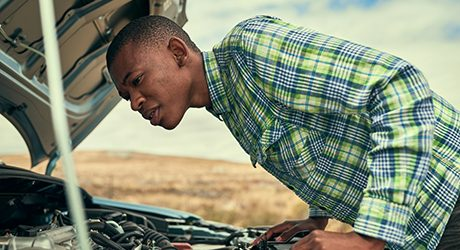 Cropped shot of a young man checking under the hood of his car after breaking down