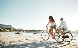 Couple on bicycles on beach