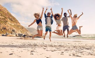 young adults jumping on the beach