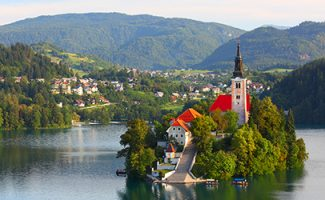 Santa Maria Church catholic church situated on an island on Bled lake with mountains and villages on the background